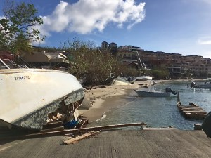 A line of beached and wrecked boats line Cruz Bay's waterfront.