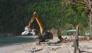 An earth-mover scoops up a load of debris at Magens Bay in October..