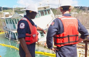 Petty Officer Ken Freeman and Lieutenant Junior Grade Henry Dumphy assess the vessel Leylon Sneed before it was refloated and returned to the owner, Wednesday. The Leylon Sneed was the last vessel removed from St John under FEMA's ESF - 10 mission. (Coast Guard Photo by Petty Officer Alex Shunda)