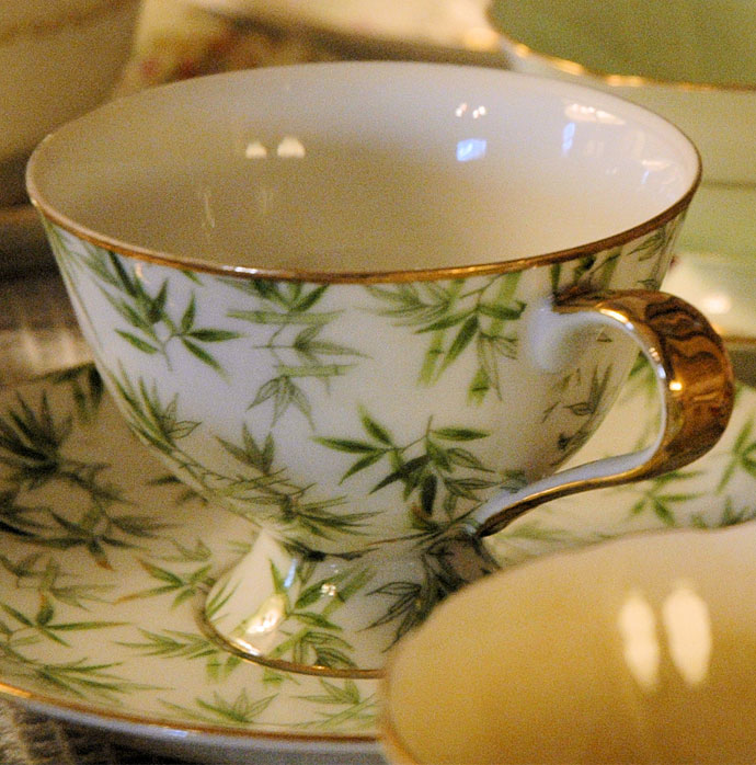 Fine china cup and saucer with green palm fronds on the outside set amid a collection of tea cups
