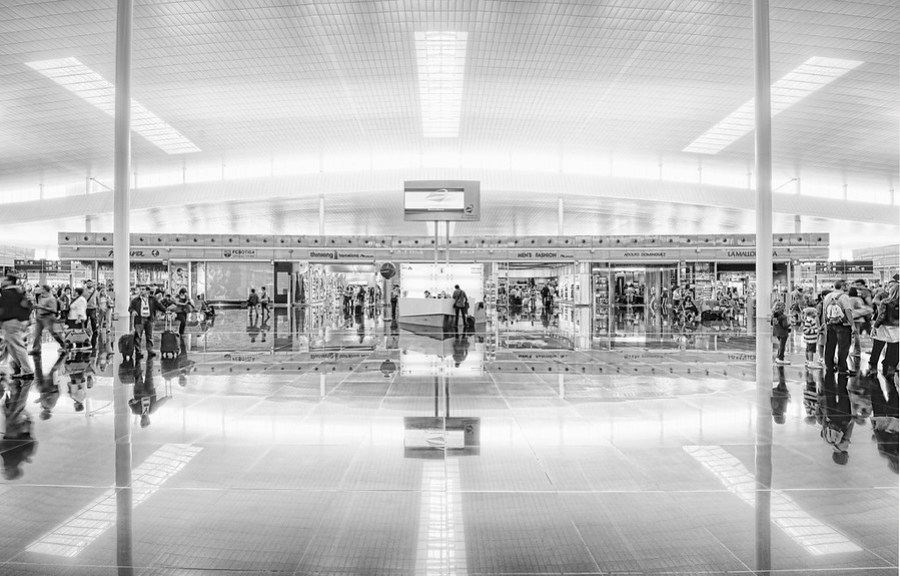 The Barcelona Airport II This is another reason I like to get to airports early.  Not only do I hate being rushed, but I like to take time to explore with my camera.  Well, I guess that only is in the case where the airport happens to be particularly beautiful, like the one here in Barcelona.  I always start out extremely rushed, because I picture security closing down on me from every angle.  So, my first shot is usually rushed and not perfectly centered.  Then, if the guards don't gang-tackle me like I'm streaking at Yankee Stadium, then I keep adjusting my position and the camera until things are more and more aligned and composed to my satisfaction.  This one was even a little bit tilted, but I fixed that bit with the crop tool later in Photoshop (as people saw).  - Trey Ratcliff Read more here at the Stuck in Customs blog.