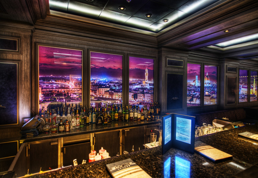 Disney Fantasy Cruise - The Skyline BarWhich city do you think this is??This is the coolest bar on the ship.  I was in here this night with John Lasseter (I think!) - but he was sitting with a group of people and I didn't want to interrupt him to say hello.  Anyway, these walls are filled with images of different cities that change out every 12-14 minutes or so.  And, if you get up close to these hi-def walls, you can see movement!  People walk around the streets, cars move, lights flicker, people go about their days inside their homes, etc.  It's endlessly fascinating.  I also have some video of this too -- I'll release that as soon as I have more bandwidth at dock!- Trey RatcliffRead the rest of this post at the Stuck in Customs blog.