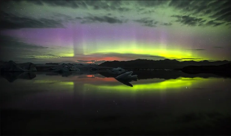 Glow from the volcanic eruption in Holuhraun is reflected in the Jokulsarlon glacial lagoon and in the heavens
