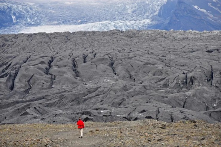 The glacial tongues of the Skaftafell glacier flows in slow motion down from the Vatnajökull  ice cap, by far the largest glacier mass in all of Europe (8,000 km2/5,500 sq. miles).   There are a number of large active volcanoes under the ice cap. The Skaftafell   glacier tongues are partially colored black by volcanic ash.