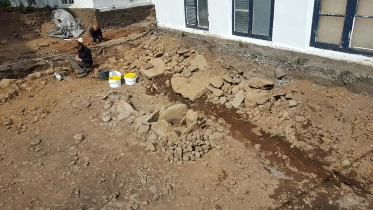 In the center of the image is the outdoor pot. The hearth is where the archaeologist is working.