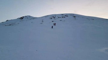 Winter hiking in Iceland. Carefully descending from Drottning Hill.