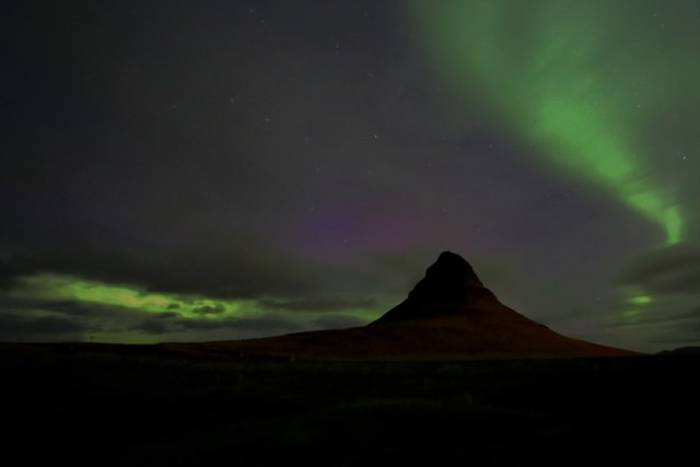 Kirkjufell mountain illuminated by the Icelandic northern lights.