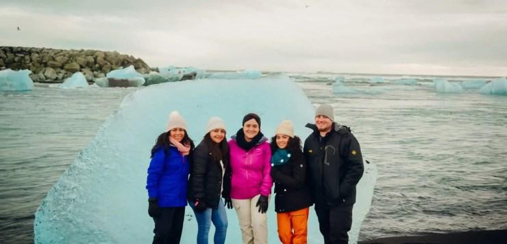 Four travelers in Iceland at the diamond beach at Breidamerkursandur beach in South East Iceland.