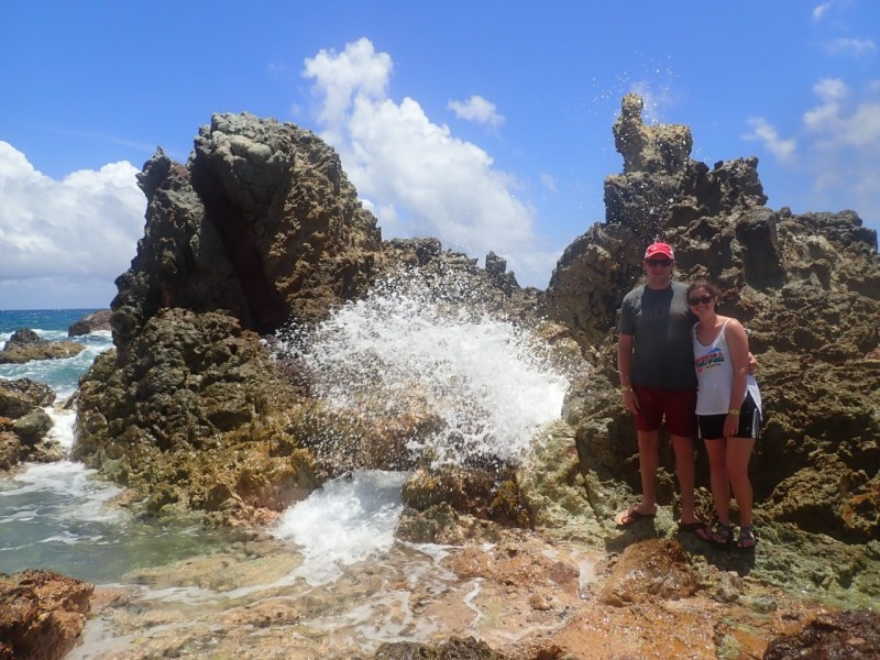 Rocky coastline with water spraying through a geyser hole and man & woman beside it.