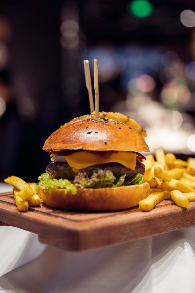 A cheeseburger with a sesame seed bun and french fries on a wooden board. One of my favorite steps to plan a dream vacation is looking at the restaurants.