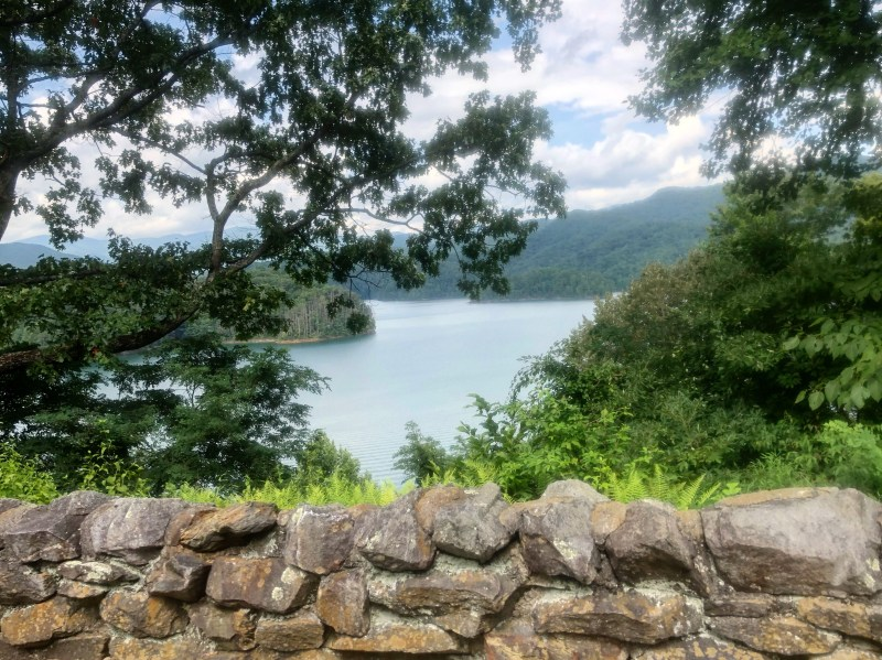The view of a lake between tree branches with a low rock wall.
