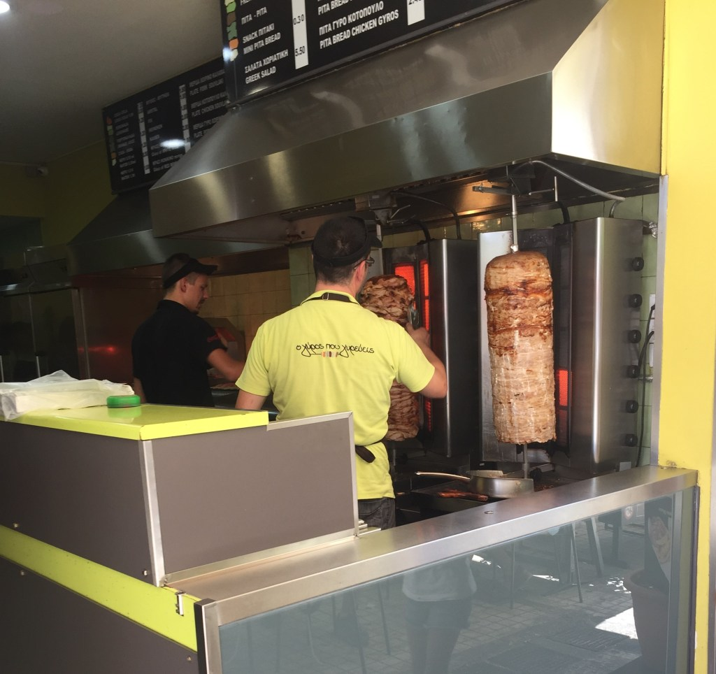A gyro shop where the employee is shaving the meat off the rotisserie.