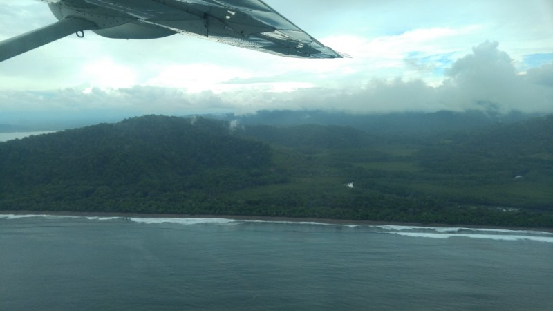 View of a beach from an airplane. When you budget for your trip be sure to consider all flights.