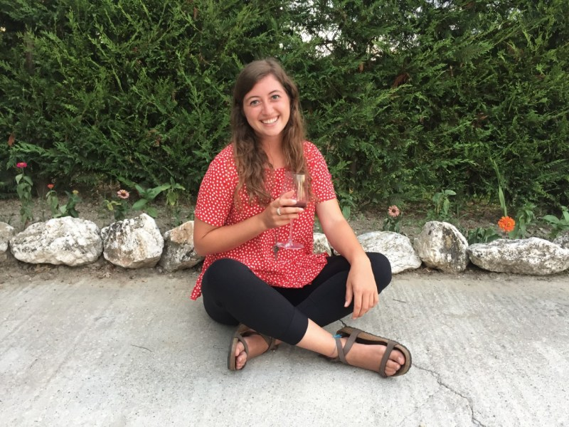 Girl with wine glass in front of greenery. I am diligent about saving money to travel.