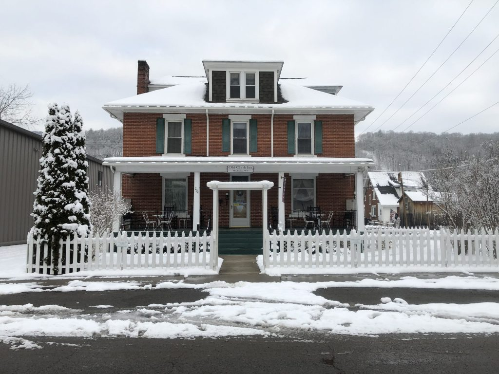 The Old Clark Inn in Marlinton is located just south of Snowshoe, West Virginia. Surrounded by a white picket fence with evergreen trees in the yard, it has a nice porch that people can use in the summer.