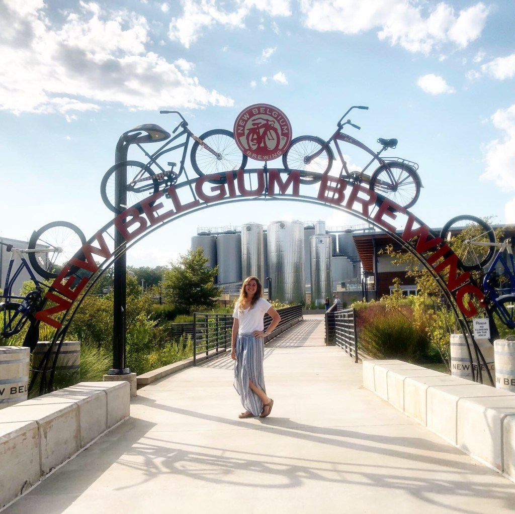 The New Belgium Brewing sign arched over a sidewalk with bicycles on top of the arch. Located in the River Arts District Asheville's many breweries make it one of the best places to visit in North Carolina.