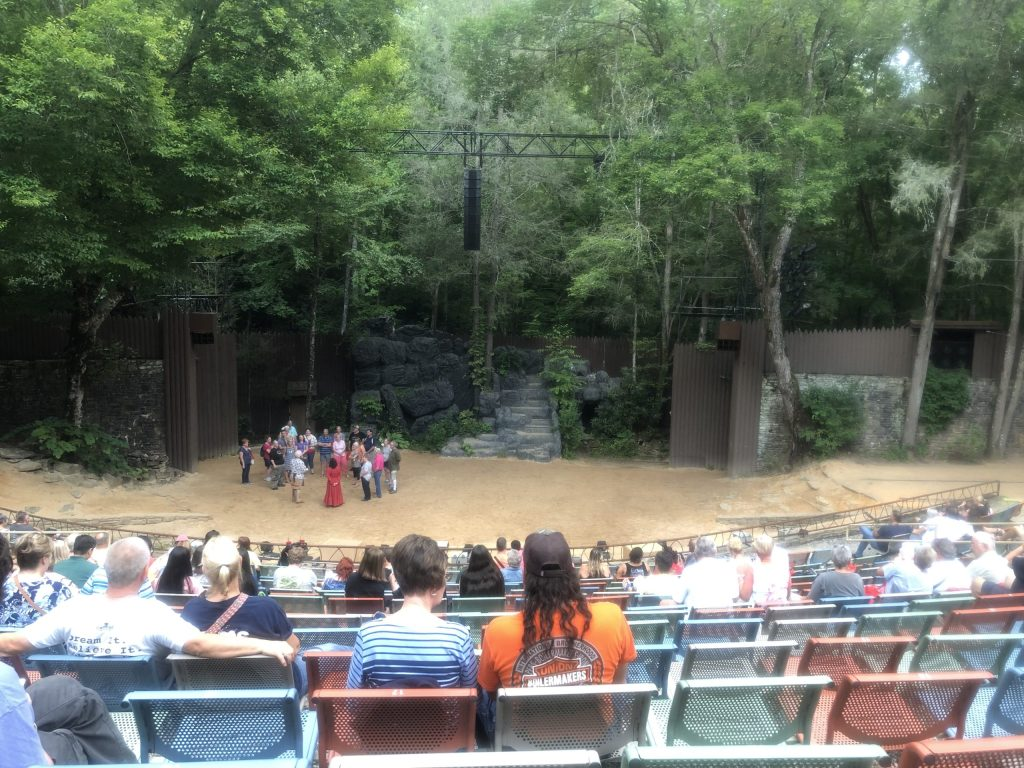 "The stage for ""Unto These Hills"" is outdoors with a dirt floor and natural backdrop. There are trees and rocks as the background."