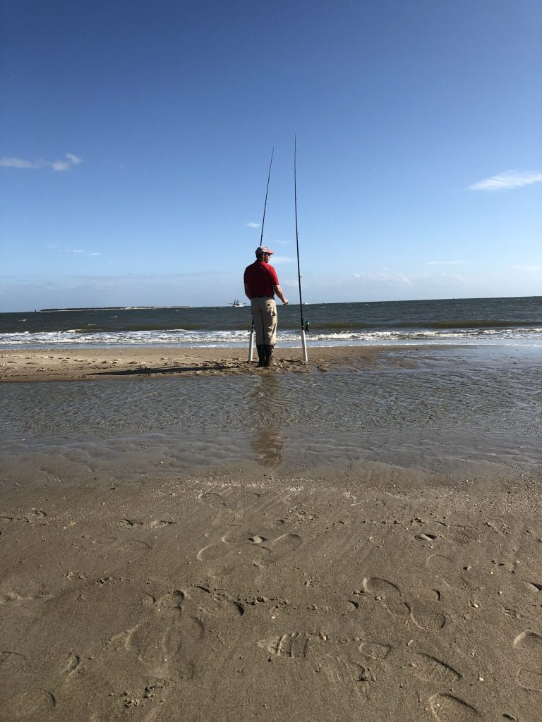 Surf fishing with two long fishing poles on the beach. Atlantic Beach is one of the best places to visit in North Carolina.