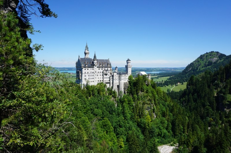Neuschwanstein Castle from the bridge across the canyon. blue sky in the backgroudn with greenery surrounding the castle. Neuschwanstein is a huge reason to visit Bavaria, Germany.