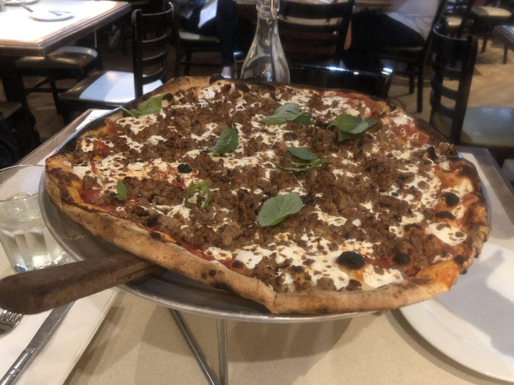 Pizza with sausage and basil. Make sure to eat pizza if you want to spend a weekend in New York City.