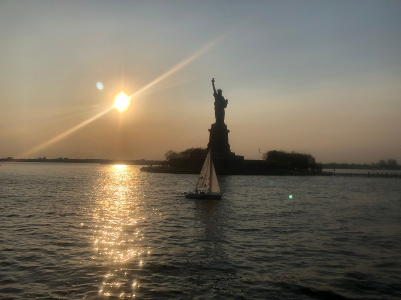 The statue of liberty at sunset with a sailboat in front of it. I save money for travel so I can see these things.