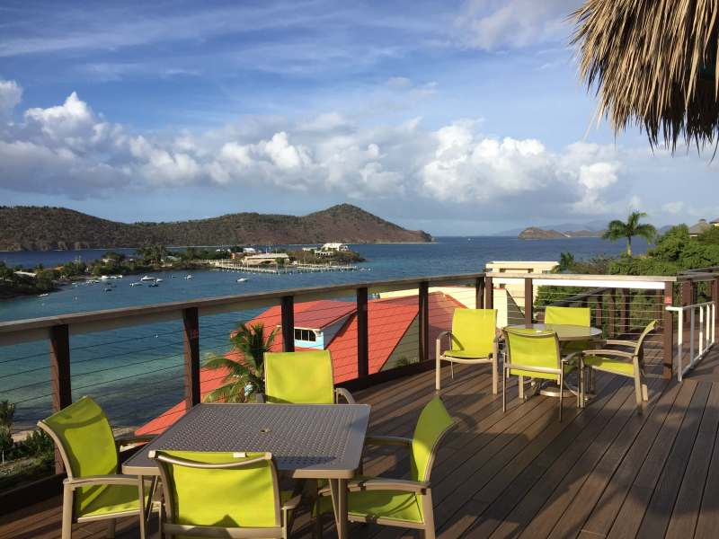 A view of the ocean from the hillside pool at Margaritaville St. Thomas with mountains in the background and colorful chairs in the foreground.