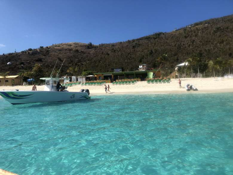 A boat on the ocean with a bar in the background on Jost Van Dyke.