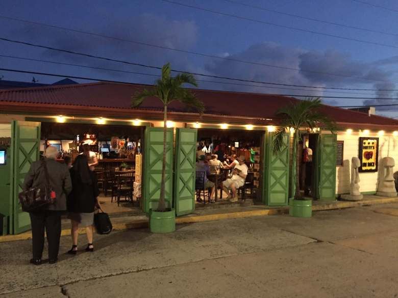 A tiki bar with green shudder doors.