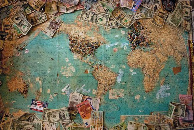 World map surrounded by money. Save money for travel.