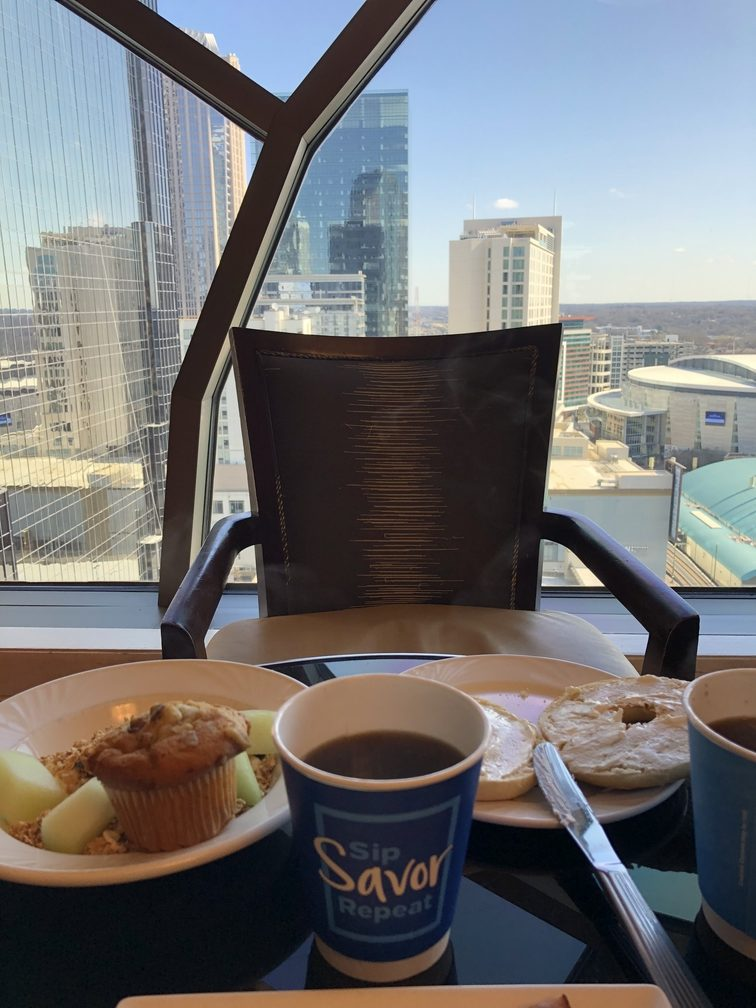 View of Charlotte skyline behind a table of breakfast food and chair. Where to stay in Charlotte.