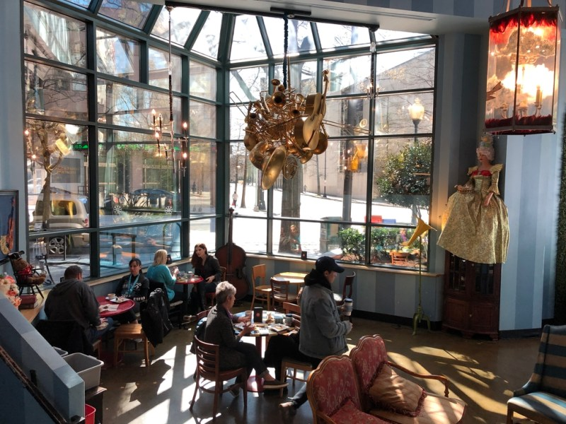 Unique light fixture in a café in front of floor-to-ceiling windows