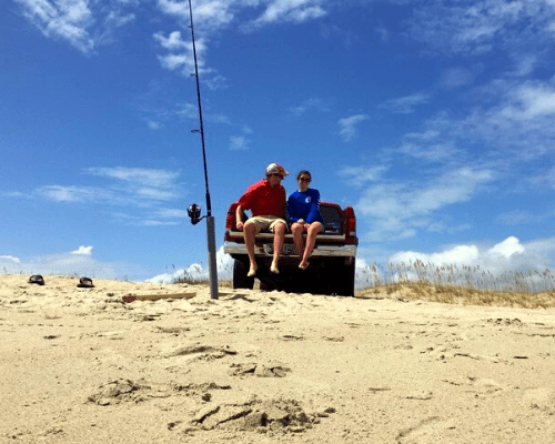 Two people sitting on the back of a truck with a fishing rod in the sand.