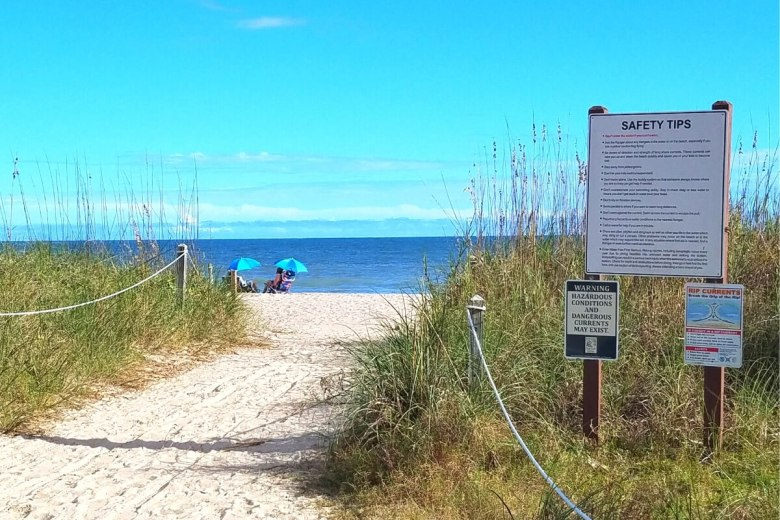 A safety sign next to a beach entrance at Edisto Island State Park.
