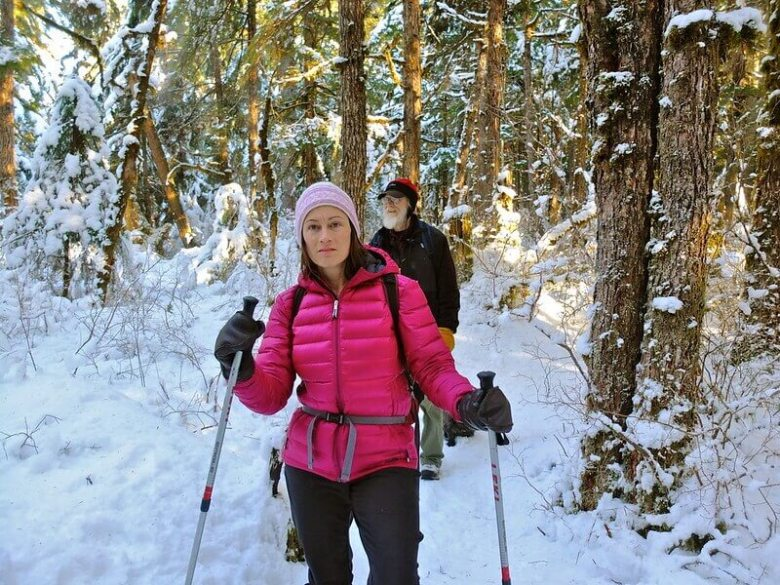 Girl with trekking poles walking through snow covered woods on a winter camping trip