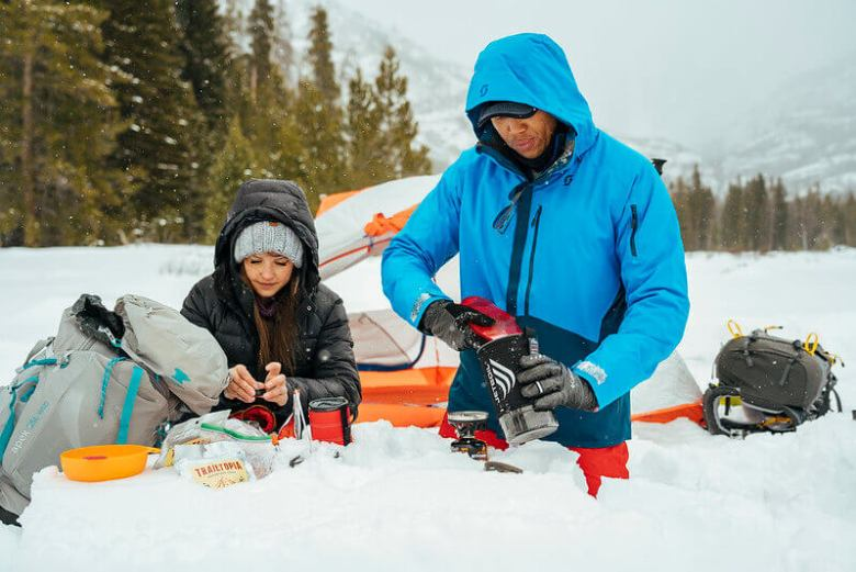 Man and woman refueling a tank for a small camping stove. Fuel is important on a winter camping trip.