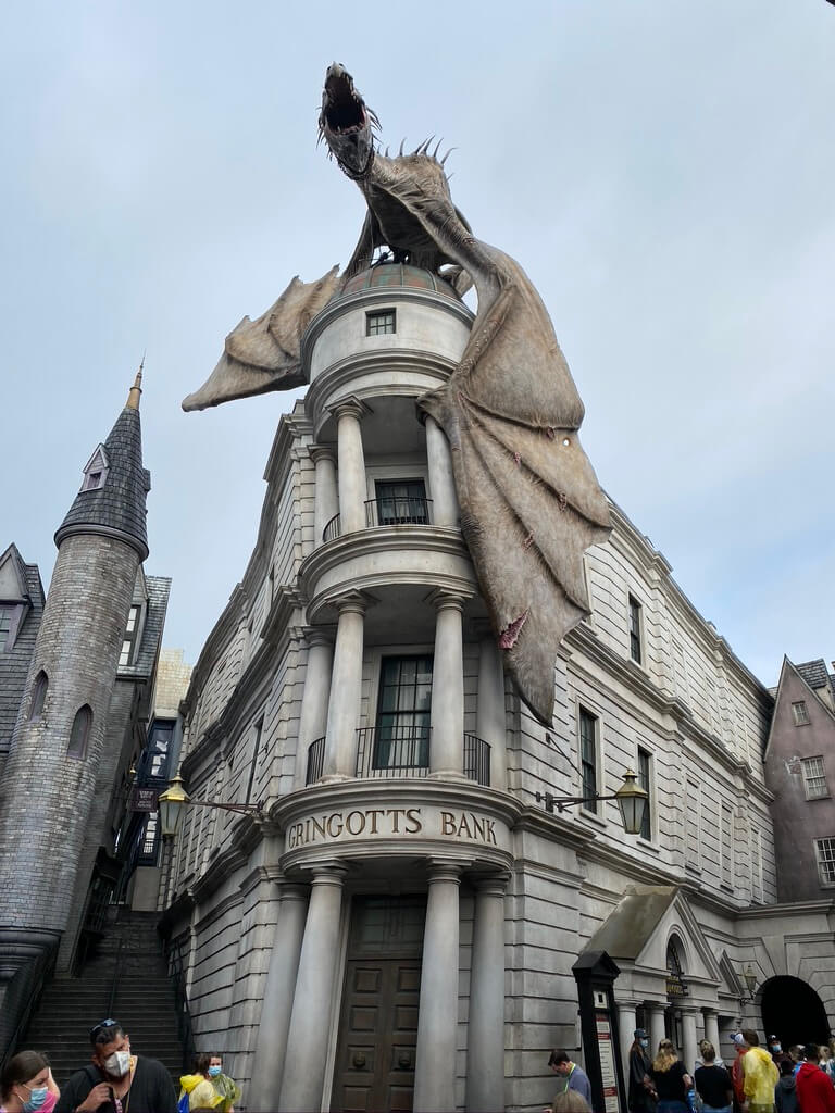 A pale dragon on top of the Gringotts three story bank. Harry Potter World Guide.