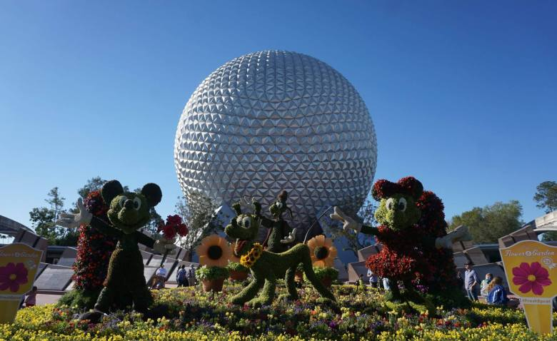 The silver dome from Epcot with characters cut out of bushes in front