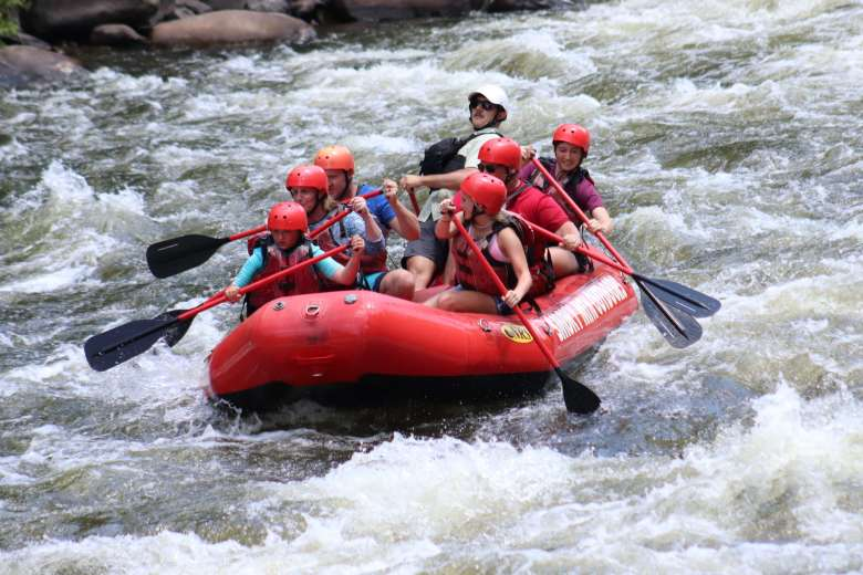 Group of people in a red raft going down the Pigeon River