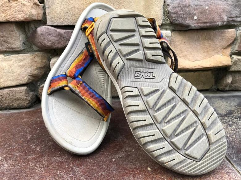 teva sandals in front of rock wall