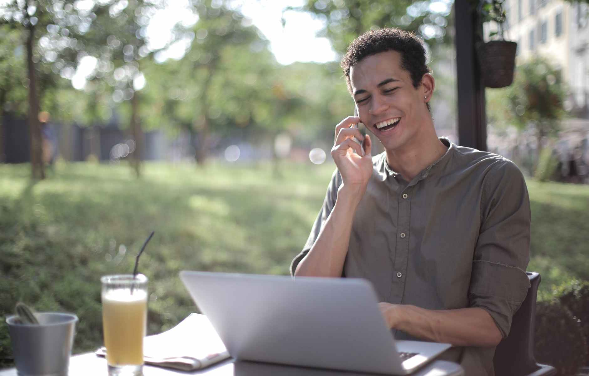 cheerful black male entrepreneur talking on smartphone in summer cafe