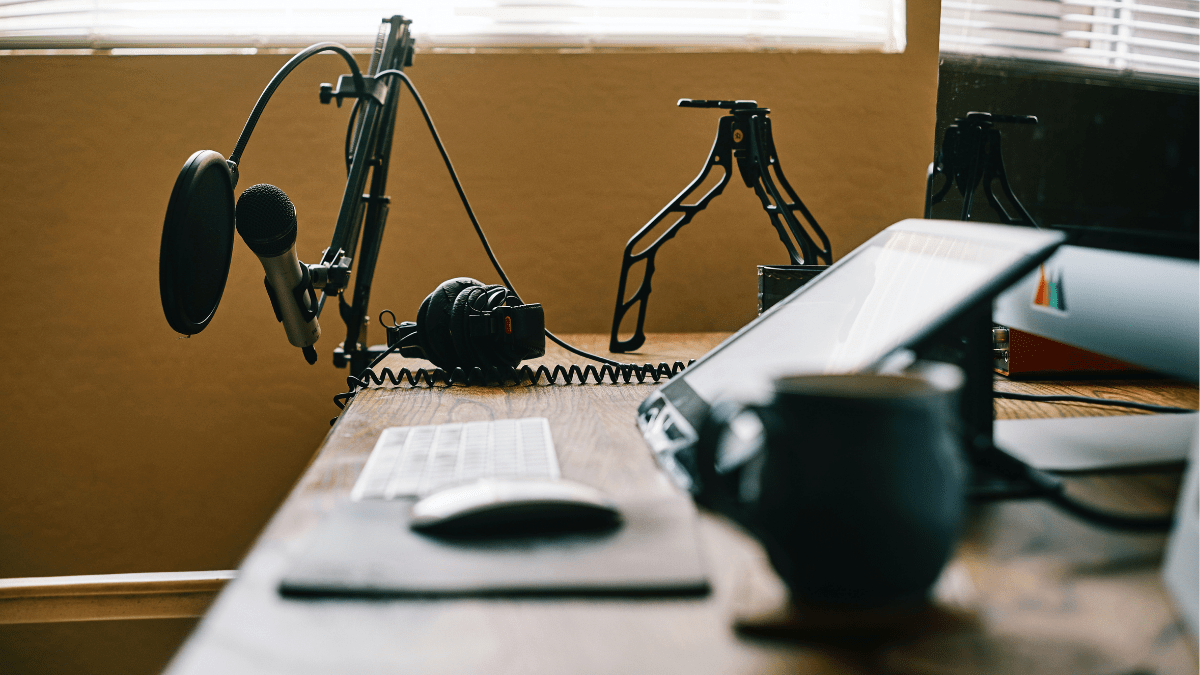 Image of podcast microphone, computer and headphones