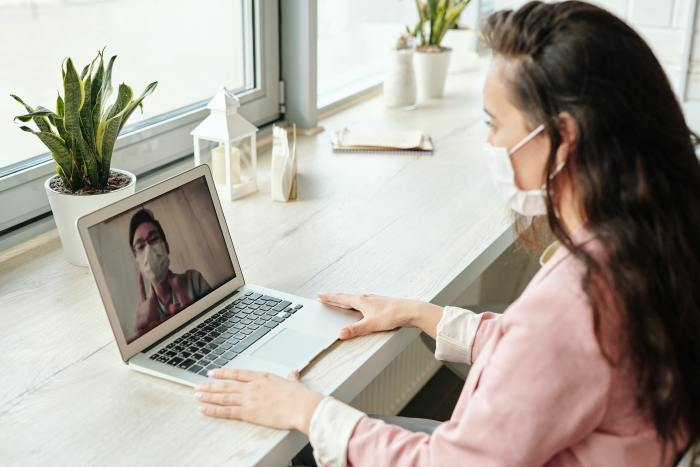 woman with a mask on looking at a laptop where there is a video of someone with a mask on
