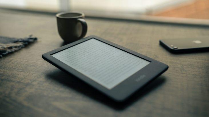 E-reader on table next to coffee mug.