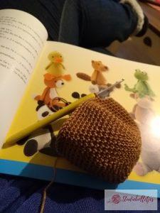Foto van overzicht van knuffels in het boek met daarvoor een haakwerkje met haaknaald.