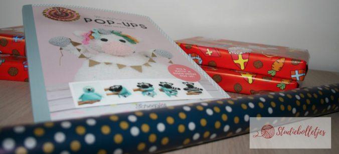 boek pop-ups op een stapel cadeau in sinterklaas papier en kerstpapier