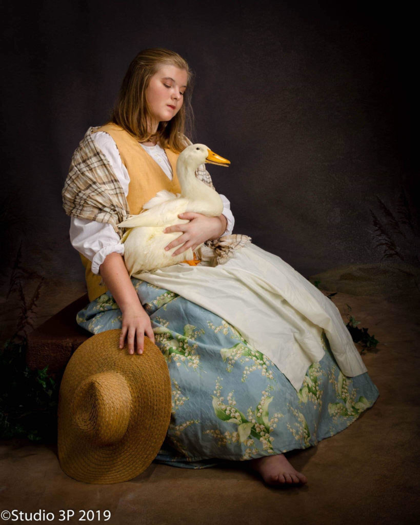 portrait of farm girl holding duck