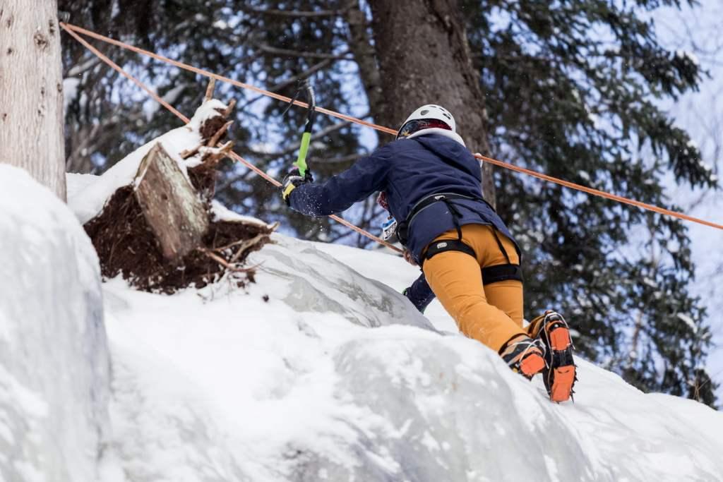 personne grimpant sur une paroi de glace