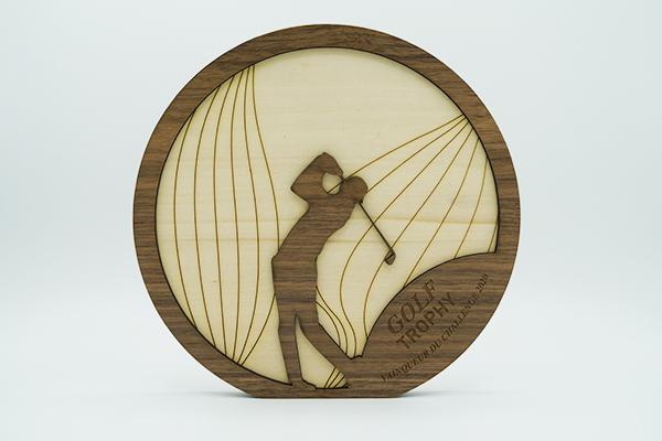 trophee de sport, bois foncé premier plan découpé avec silhouette de golfeur, arrière plan rond avec bois clair gravé - artisan designer de trophée, création originale Fortier