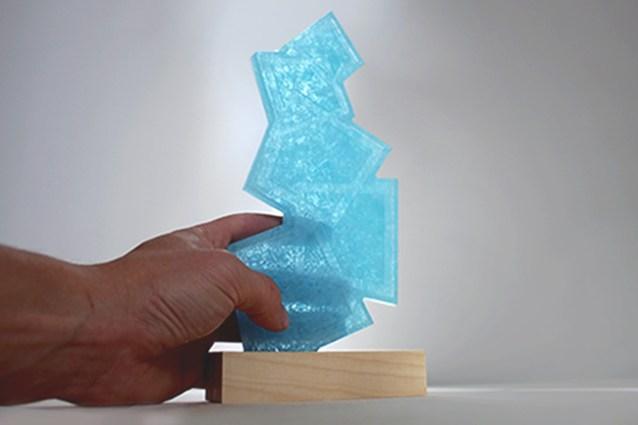 tenir un trophée haut de gamme, main lauréat avec trophée en matière recyclé, artisanat upcyclé, fronton bleu dépoli transparent à la lumière_création sur mesure de trophées durables