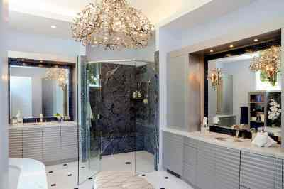 Contemporary cabinets and crystal chandelier in a luxury master bathroom